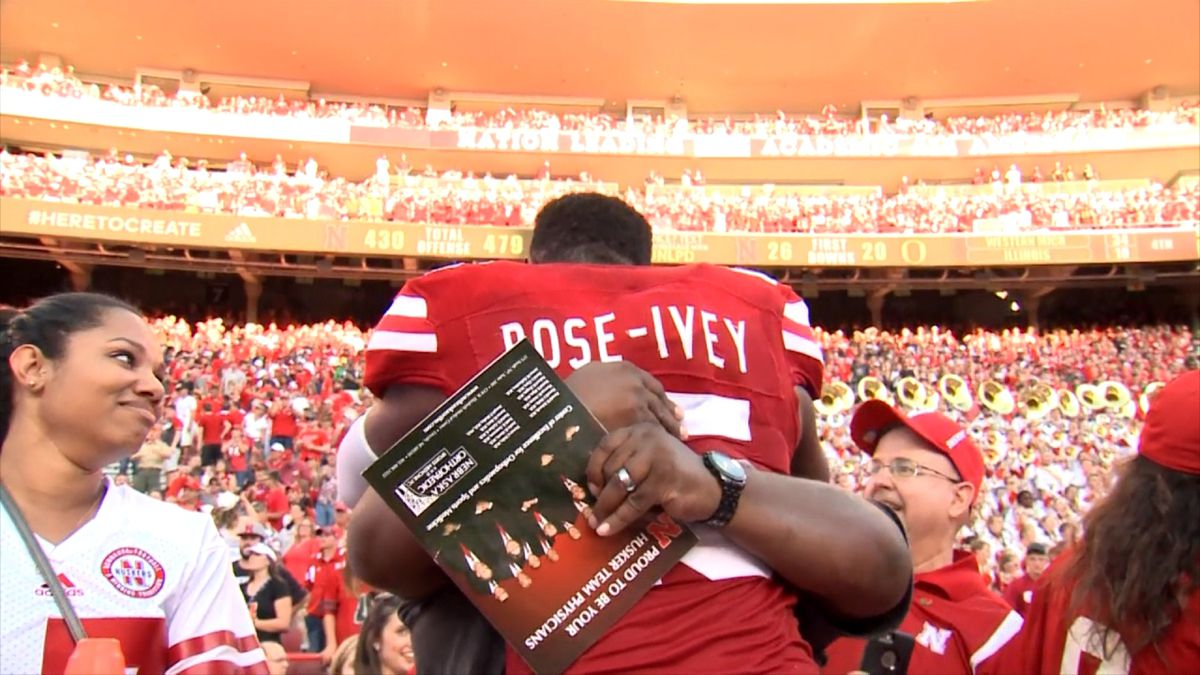 Michael Rose-Ivey hugs his father following a Nebraska football game in 2016.