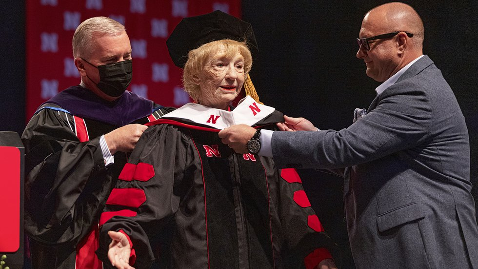 Leta Powell Drake, local television pioneer and Husker alumna, is hooded by NU Regent Tim Clare...