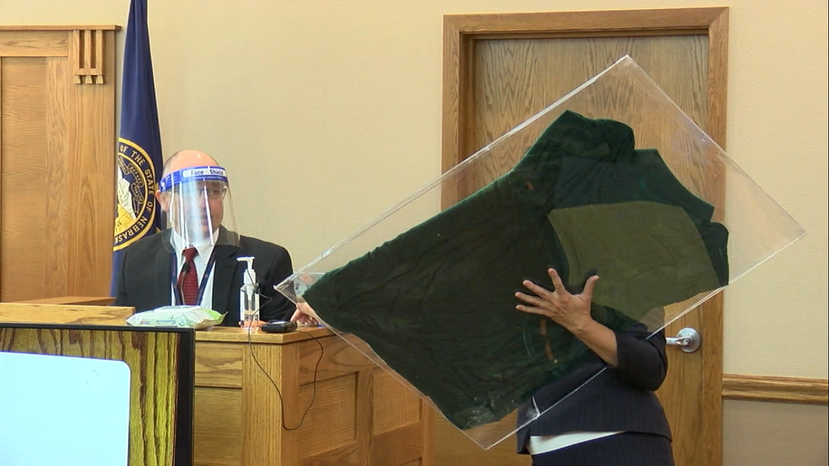 Prosecutor Sandra Allen holds up a t-shirt found in a ditch in Saline County.