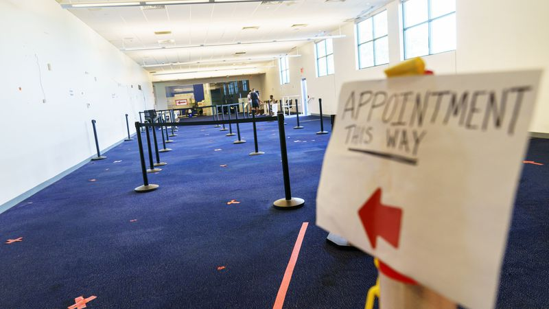 A sign points the way to a check-in area at a coronavirus mass-vaccination site at the former...