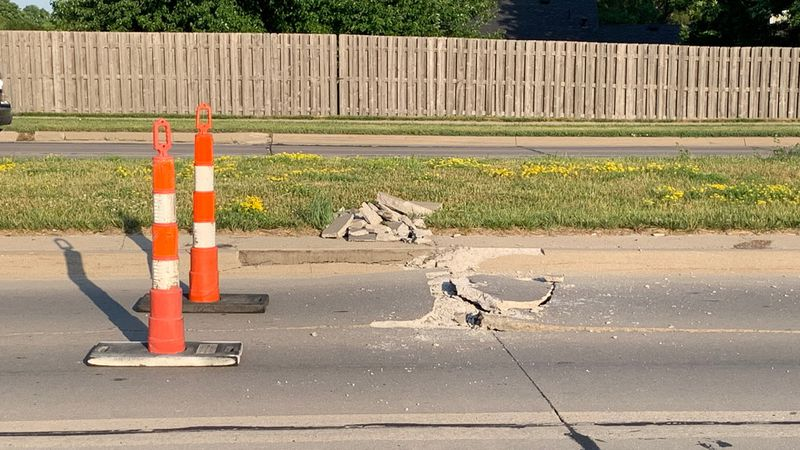 Two sections of 84th Street are cordoned off  with cones due to cracked concrete
