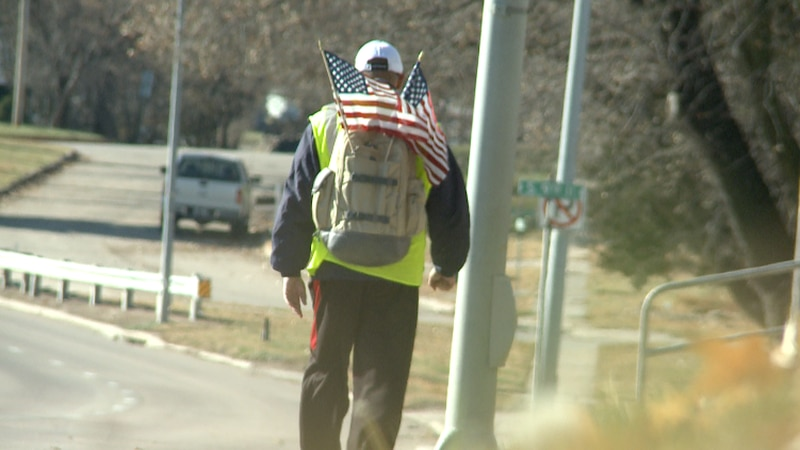 With a bright vest and American flags coming out of his backpack, Gene Curtis is walking 100...