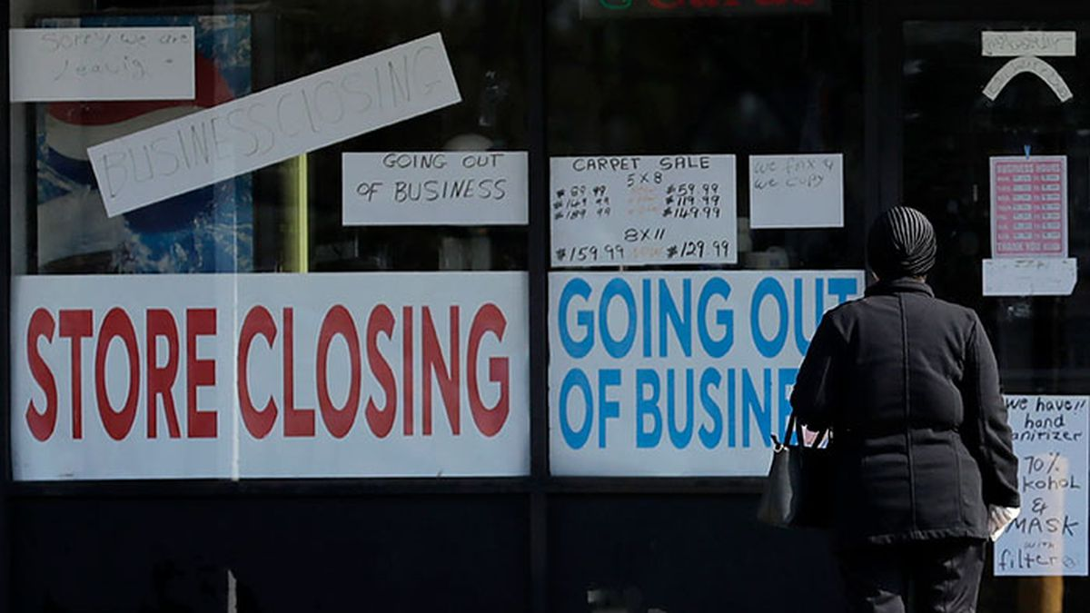 A woman looks at signs at a store closed due to COVID-19 in Niles, Ill., Wednesday, May 13,...