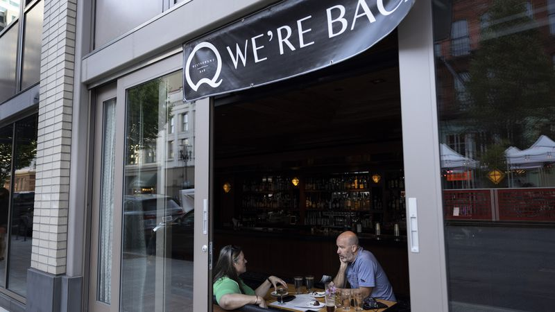 FILE - In this June 4, 2021, file photo, people dine at the Q restaurant and bar after a...