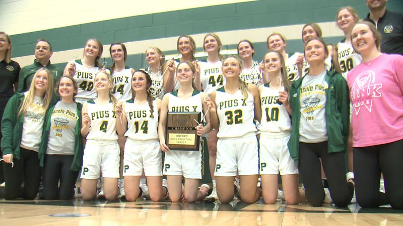 Lincoln Pius X players and coaches pose with the District A-1 Championship plaque.