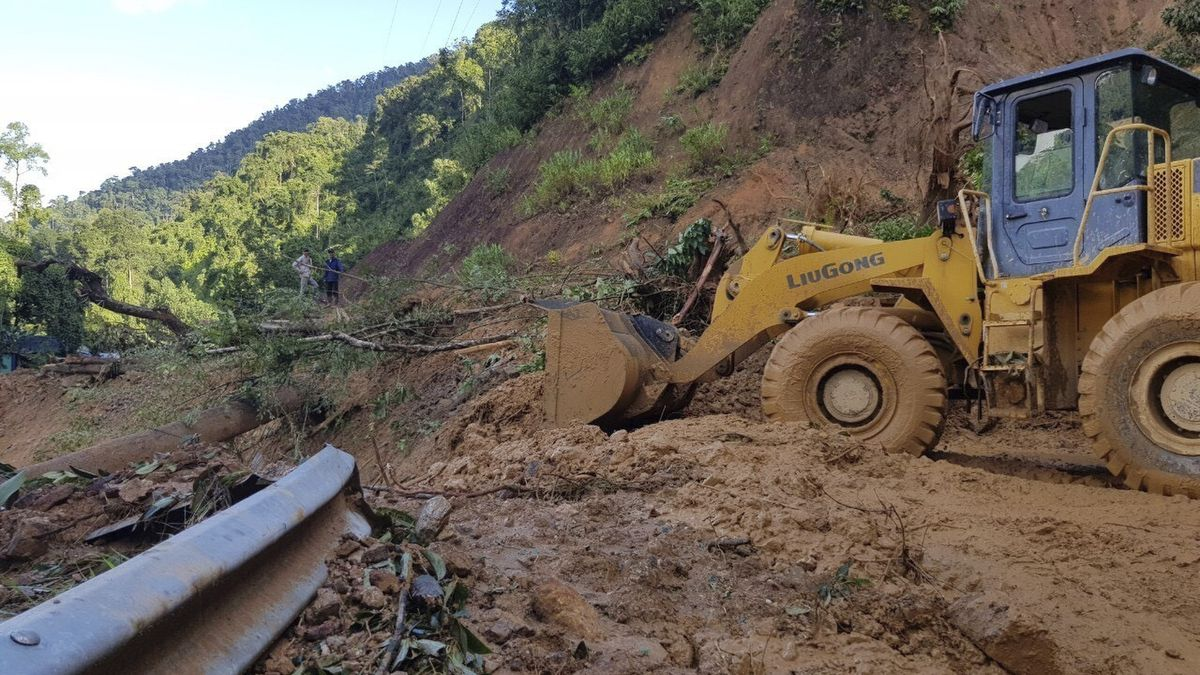 A bulldozer clears out the road damaged by a landslide to access a village swamped by another...