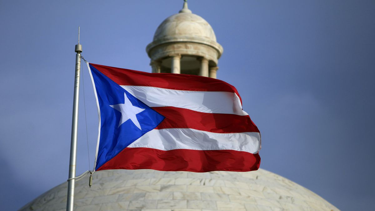 FILE - In this July 29, file 2015 photo, the Puerto Rican flag flies in front of Puerto Rico's...