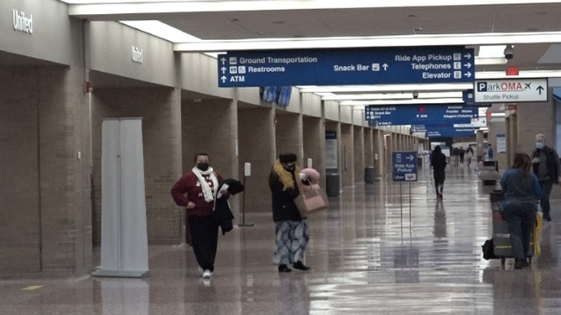 Travelers walk through Eppley Airfield Dec. 18, 2020