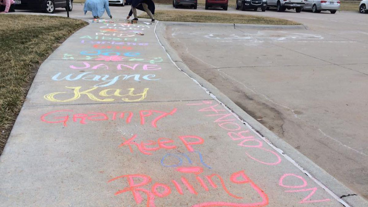 People wrote chalk messages to family members quarantined inside The Heritage at Sagewood because of the coronavirus Sunday afternoon. (Source: Kelsey Dickeson, KSNB)