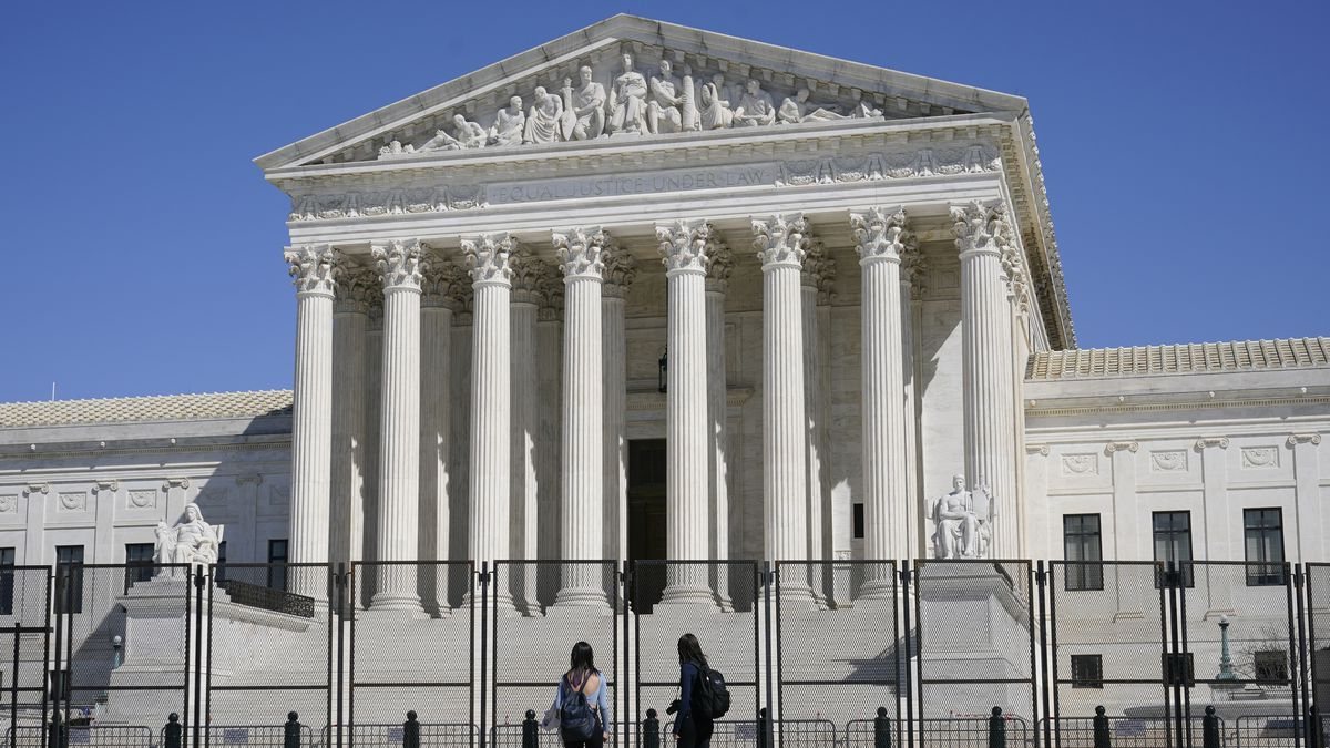 FILE - People view the Supreme Court building from behind security fencing on Capitol Hill in...