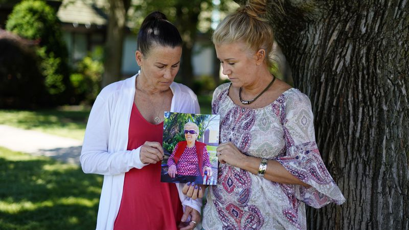 Angela Ermold, right, and her sister, Denise Gracely, hold a photo of their mother, Marian...