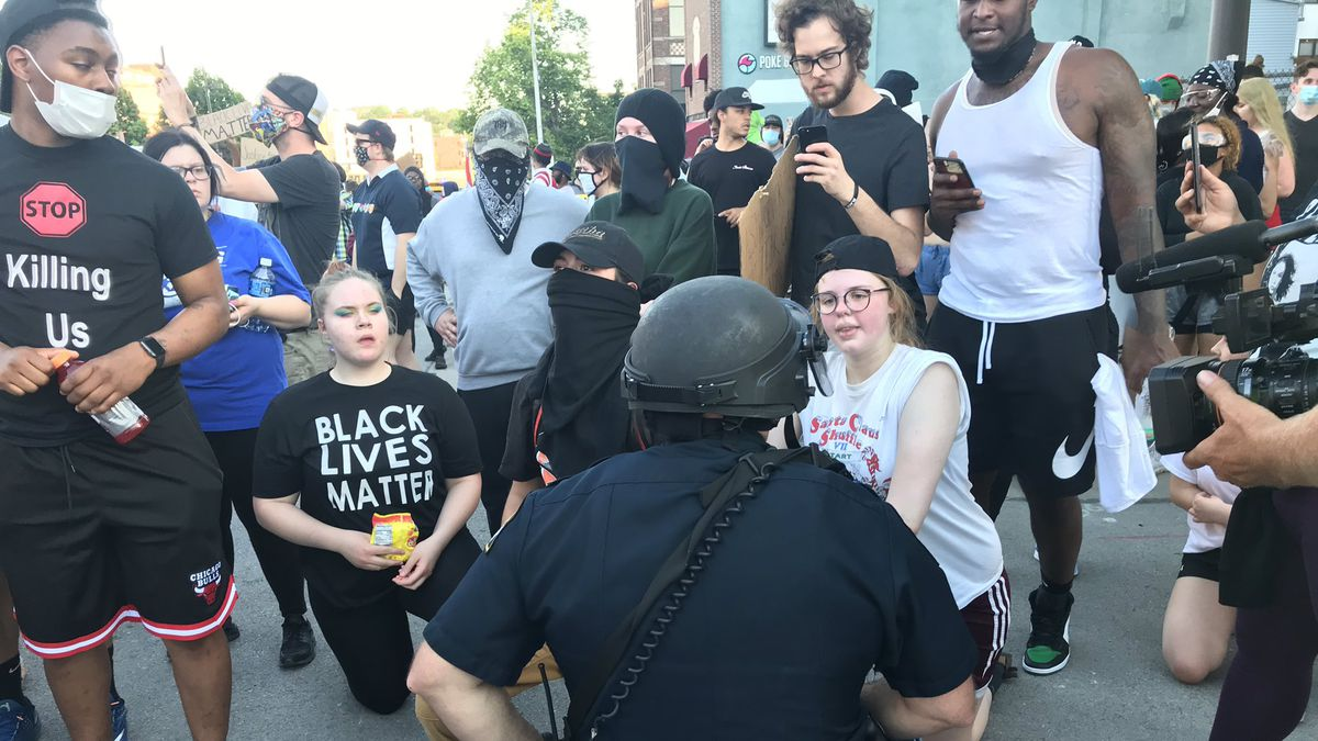 An Omaha Police kneels with protesters Monday, June 1, 2020, in the Old Market area of downtown Omaha. OPD Deputy Chief Ken Kanger said police asked protest leaders that if both sides took a knee, that protesters would comply with the order and leave peacefully. (WOWT)