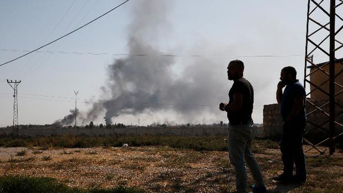 In this photo taken from the Turkish side of the border between Turkey and Syria, in Akcakale, Sanliurfa province, southeastern Turkey, people watch as smoke billows from targets inside Syria during bombardment by Turkish forces Thursday, Oct. 10, 2019. (AP Photo/Lefteris Pitarakis)