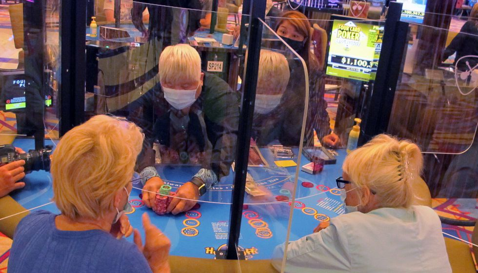 See-through barriers separate gamblers and a dealer at a card table at the Hard Rock casino in...