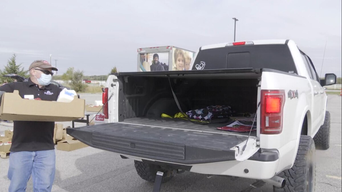 A Food Bank of Lincoln staff member loads food into the back of a truck during a drive through...