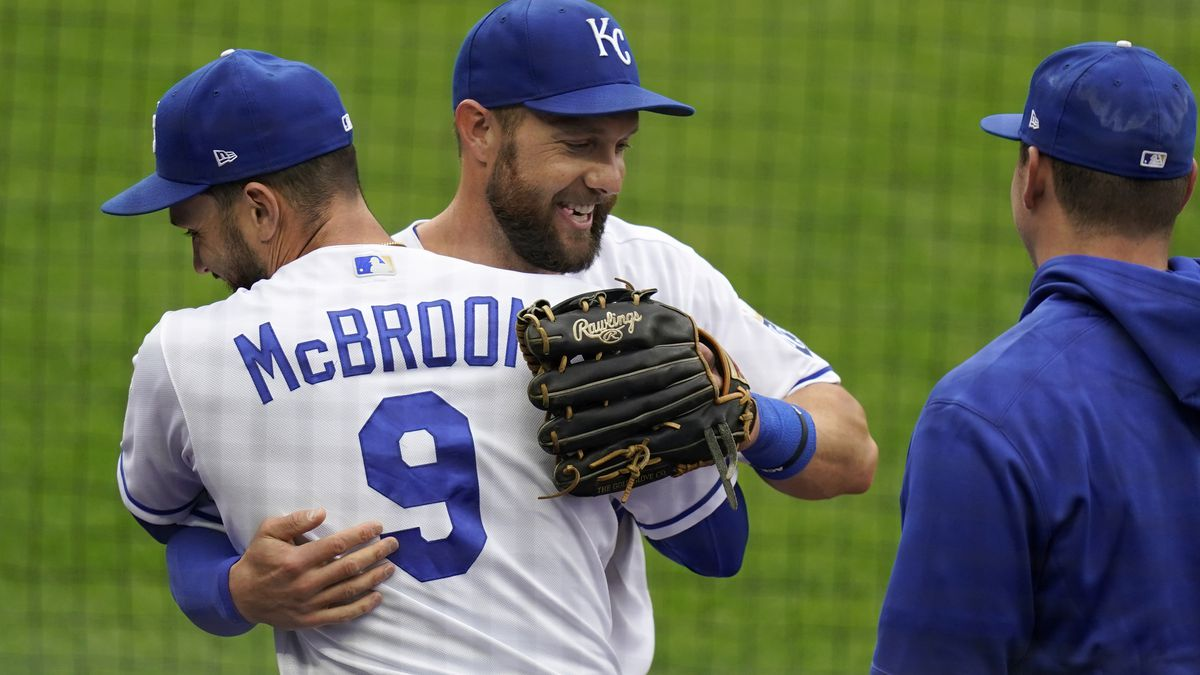 Kansas City Royals left fielder Alex Gordon, middle, is hugged by teammate Ryan McBroom (9) after being taken out of a baseball game against the Detroit Tigers during the second inning at Kauffman Stadium in Kansas City, Mo., Sunday, Sept. 27, 2020. It was Gordon's last game as a Royal. (AP Photo/Orlin Wagner)