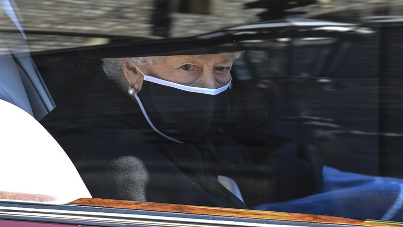 Britain's Queen Elizabeth II follows the coffin in a car as it makes it's way past the Round...
