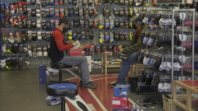 The owner of The Lincoln Running Company helps a customer buy a new pair of shoes.