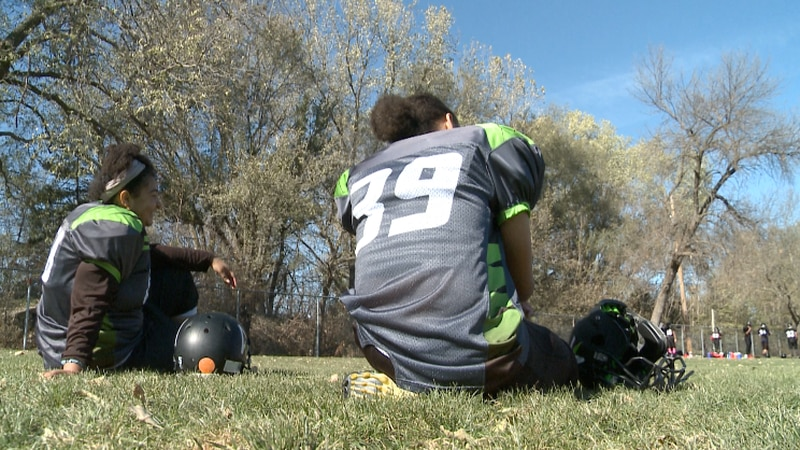 Hallie Harris and Nina Thomas watch from the sideline as the Lincoln Youth Football playoffs go...