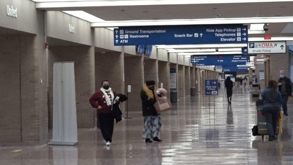 Travelers walk through Eppley Airfield Dec. 18, 2020